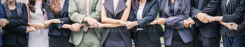 Idérikt lag som tillsammans sätter deras händer, begrepp för baner för teamwork för affärsfolk