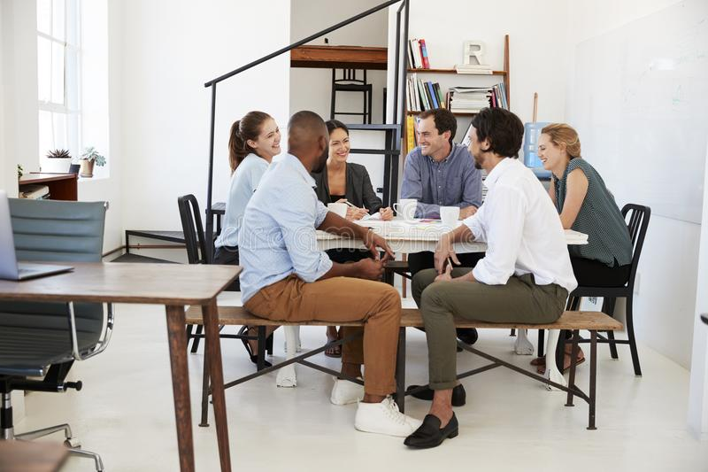 Idérikt lagmöte runt om en tabell i ett kontor royaltyfri fotografi