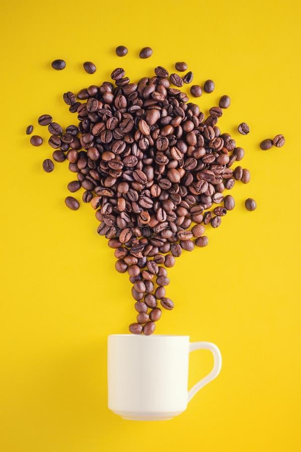 Idérikt matfoto Kaffebönor som exploderar med fyrverkerier från en kopp på en gul bakgrund arkivbild