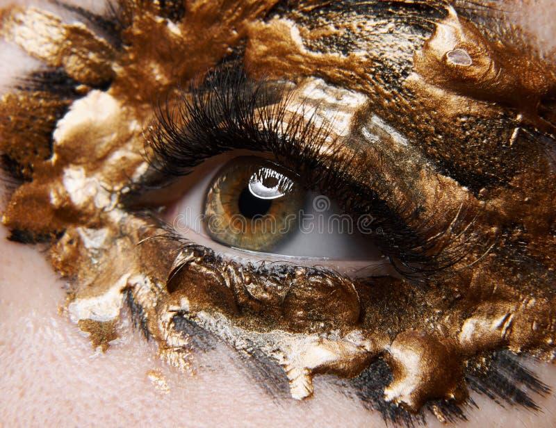 Idérikt sminktema för makro och för närbild: härligt kvinnligt öga med guld- svart målarfärg, retuscherat foto royaltyfri fotografi