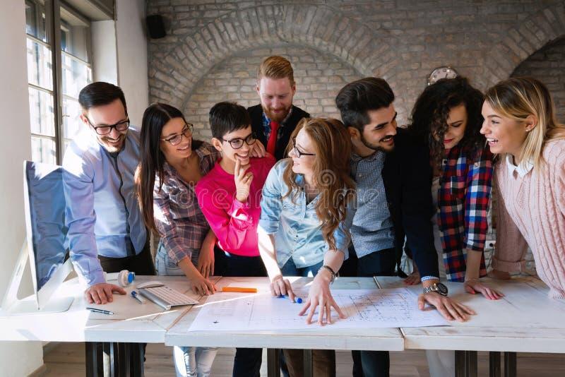 Idérikt ungt affärsfolk och arkitekter som i regeringsställning arbetar arkivfoton