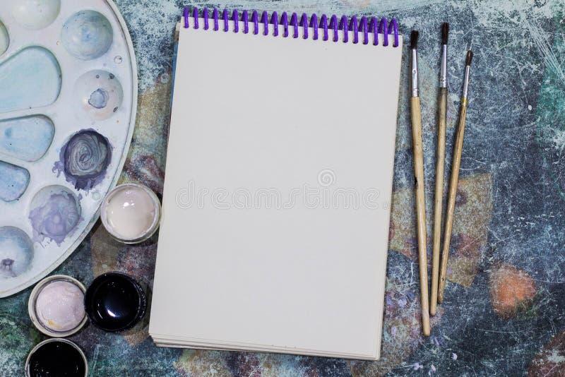 Idérikt utrymme Det funktionsdugliga utrymmet av konstnären på den sjaskiga tabellen: målarfärggouachen, anteckningsbok, borstar fotografering för bildbyråer