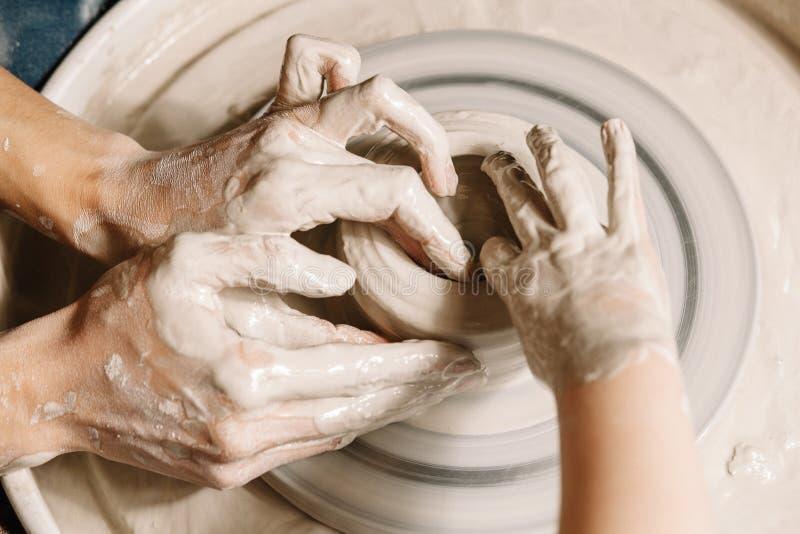 Id?es de professions Potier de femme enseignant l'art de la fabrication de pot Fonctionnement d'enfant sur la roue de potiers fai image stock