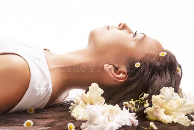 Id?es de soins de sant? Portrait de la femme caucasienne tranquille de brune s'?tendant sur le plancher et ayant des cheveux avec photo libre de droits