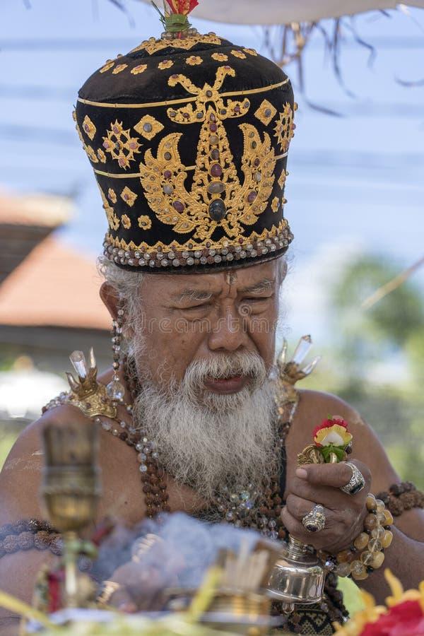 Ida Pedanda Gede Made Gunung un alto sacerdote hindú, conduce rezo religioso durante hizo una oferta ceremonia de la cremación en fotografía de archivo