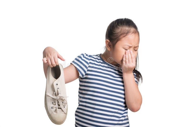 Idade asiática da menina da criança sapata fedido da posse de 7 anos no fundo branco foto de stock