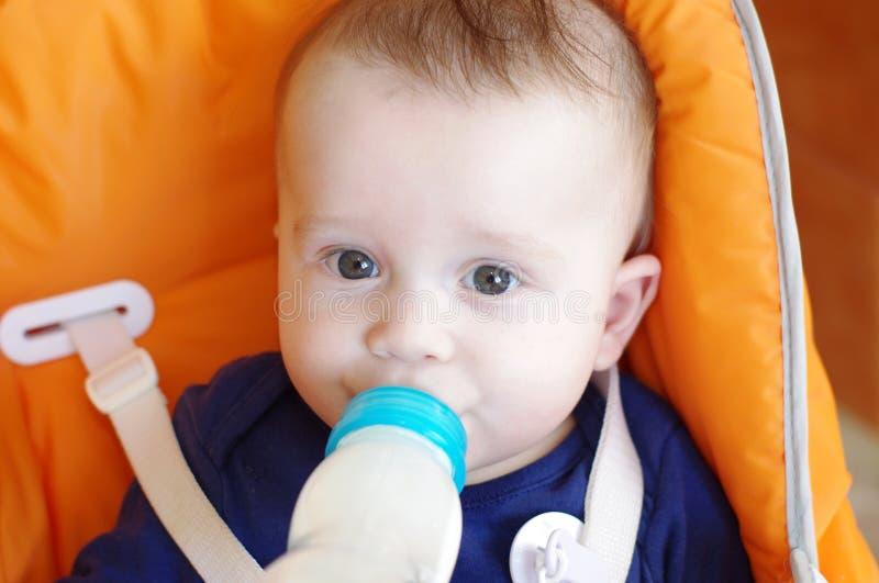 A idade do bebê de 6 meses come da garrafa pequena foto de stock
