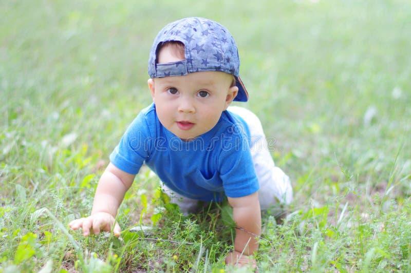 A idade do bebê de 10 meses rasteja na grama no verão foto de stock royalty free