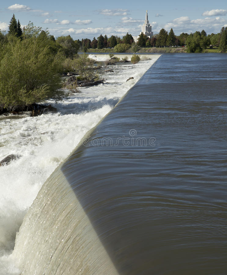 Idaho Falls. The waterfall in Idaho Falls is the town landmark with a park on both sides. The sharp diagonal lines from the dam provide nice leading lines to the stock photo