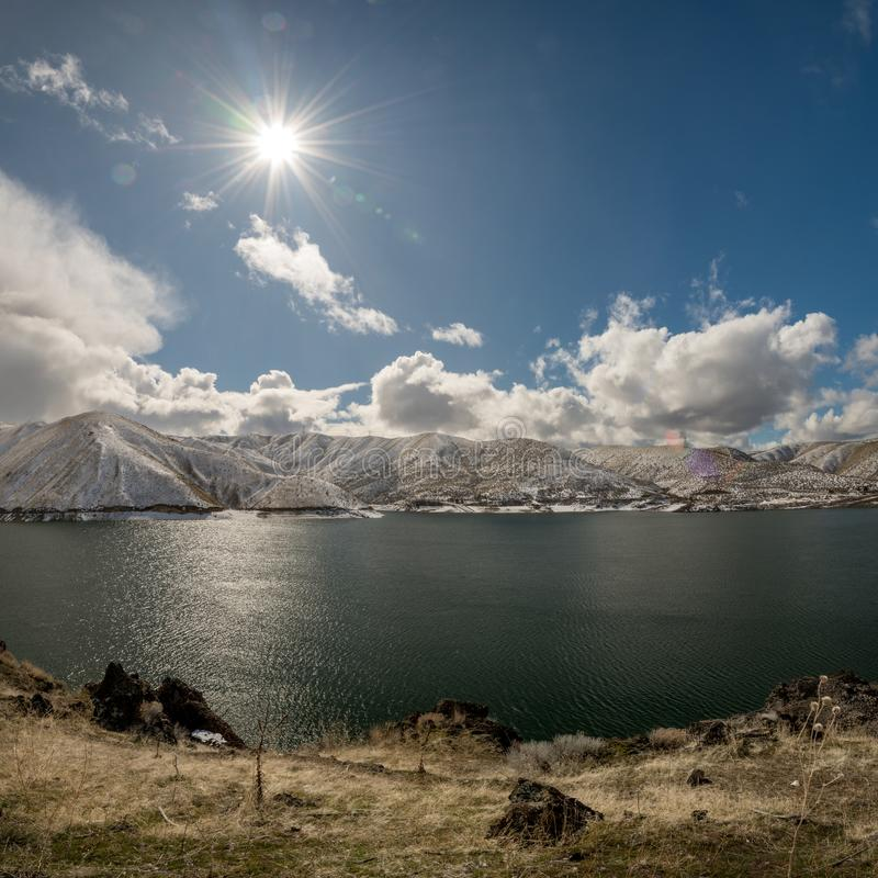 Sun star over the Luck Peak reservoir in winter with snow in the stock photography