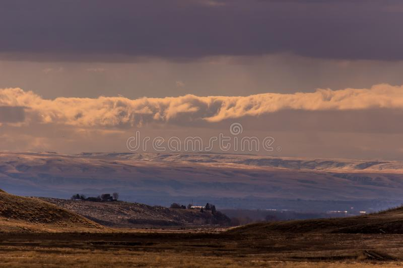 Idaho Ranch at sunset after a light snow under blue sky and broken clouds. Idaho foot hills Ranch after a light snow under blue sky and broken clouds. North of stock photos