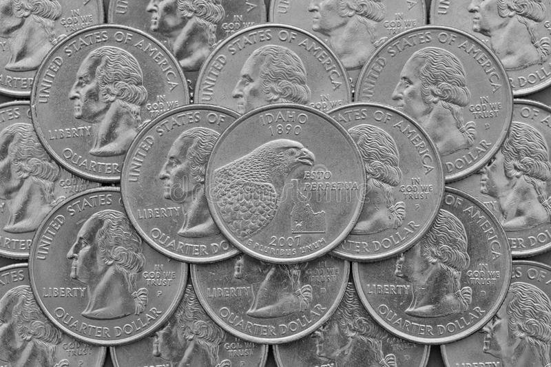 Idaho State and coins of USA. Pile of the US quarter coins with George Washington and on the top a quarter of Idaho State royalty free stock photography