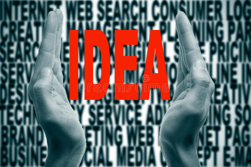Idea. Man hands forming brackets and the word idea written in red inside, on a background full of words about internet concept stock photo