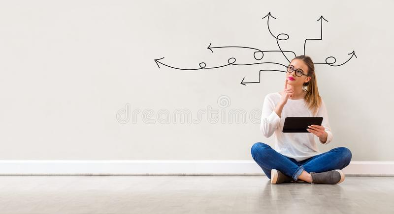 Idea arrows with woman using a tablet. Idea arrows with young woman holding a tablet computer stock image
