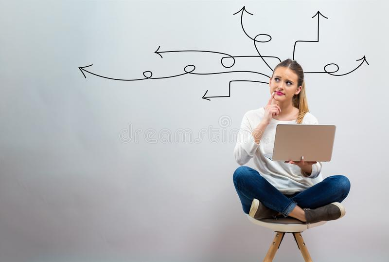 Idea arrows with young woman using her laptop. On a grey background royalty free stock photos