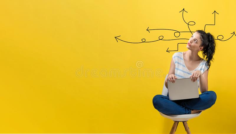 Idea arrows with woman using a laptop. Idea arrows with young woman using a laptop computer stock image