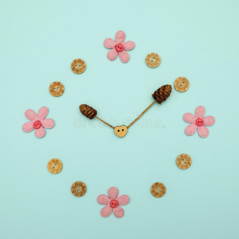 Idea. Clock made of flowers at 10.00 on blue background, The concept of time stock photography