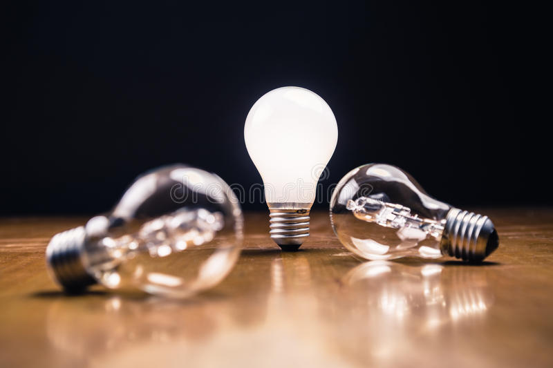 Idea. Comparative white light bulb standing on the table royalty free stock photo