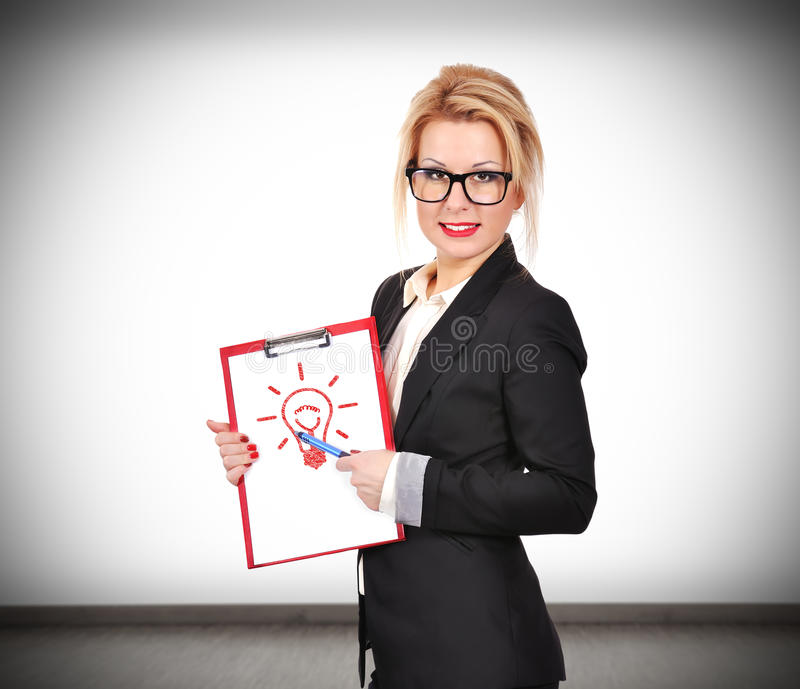 Idea concept. Businesswoman holding clipboard with lamp, idea concept royalty free stock photo