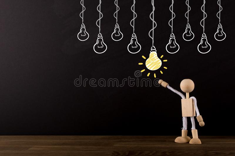 Idea concept, choosing the best idea, Brainstorming, Innovative Wooden Stick Figure pointing at a yellow light bulb royalty free stock photography