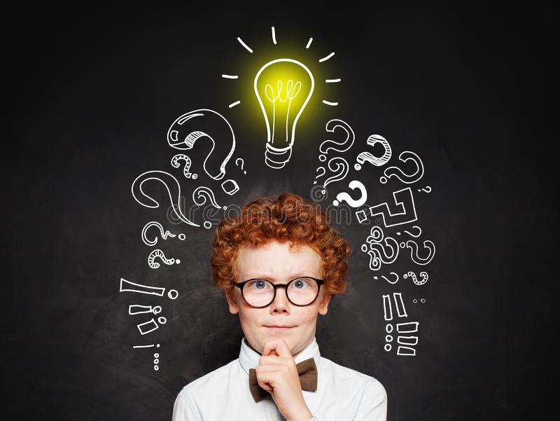 Idea concept. Cute young boy student with question marks and light bulb royalty free stock photography