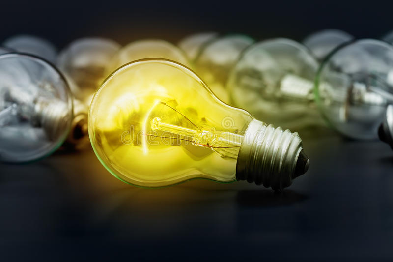 Idea concept with incandescent light bulbs. Incandescent light bulbs on dark surface with the center one lighting stock photo