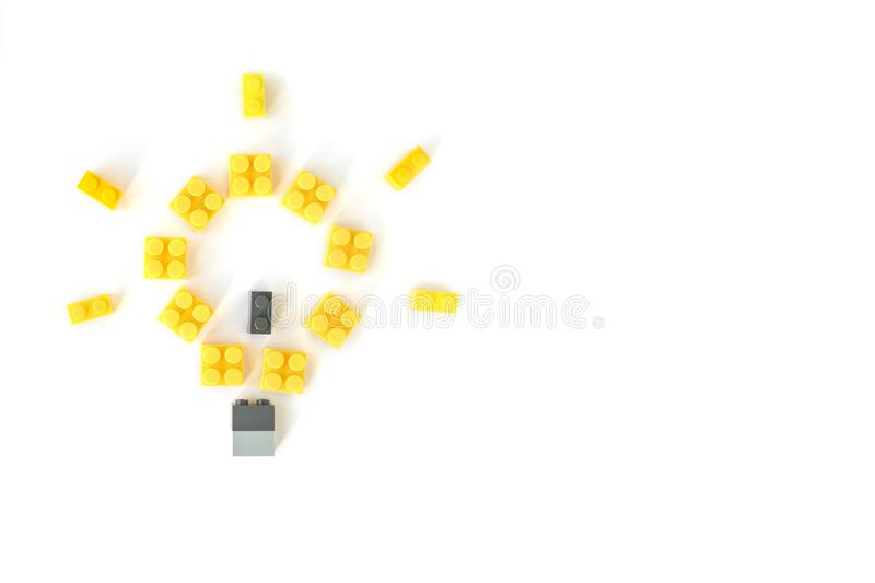 Idea concept. Lego background. Lamp made of yellow plastic constructor bricks on white background. Popular toys. Copyspace. Idea concept. Lamp made of yellow stock image