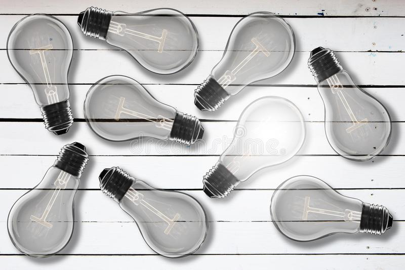 Idea concept - light bulb on the wooden desk. Idea and leadership concept - incandescent light bulb on the wooden table stock images
