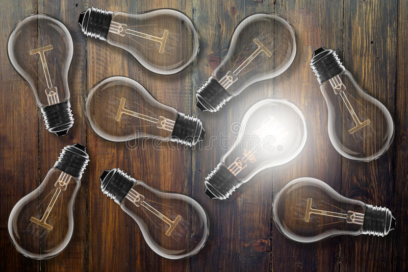 Idea concept - light bulb on the wooden desk. Idea and leadership concept - incandescent light bulb on the wooden table stock image