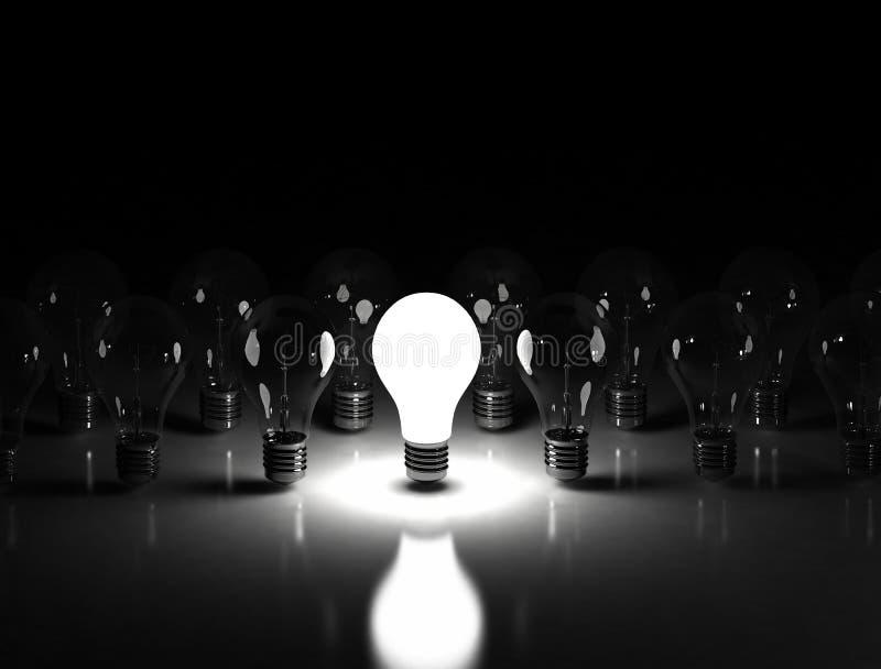 Idea concept - lit light bulb on the black background stock photography