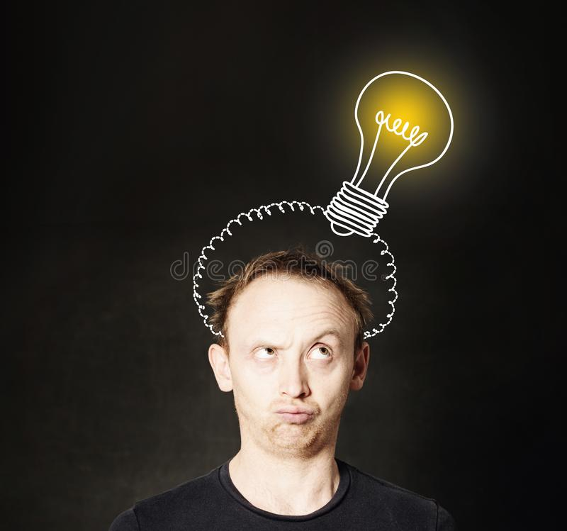 Idea concept. Man thinking on blackboard background with light bulb. Brainstorm and idea royalty free stock image