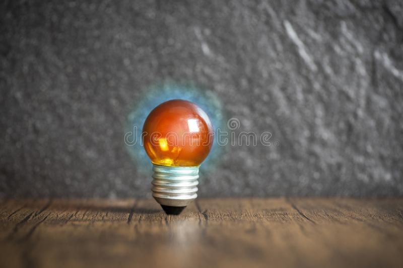 Idea concept with orange light bulb and blue light wooden with dark background. Idea concept with orange light bulb and blue light on wooden with dark background royalty free stock photography