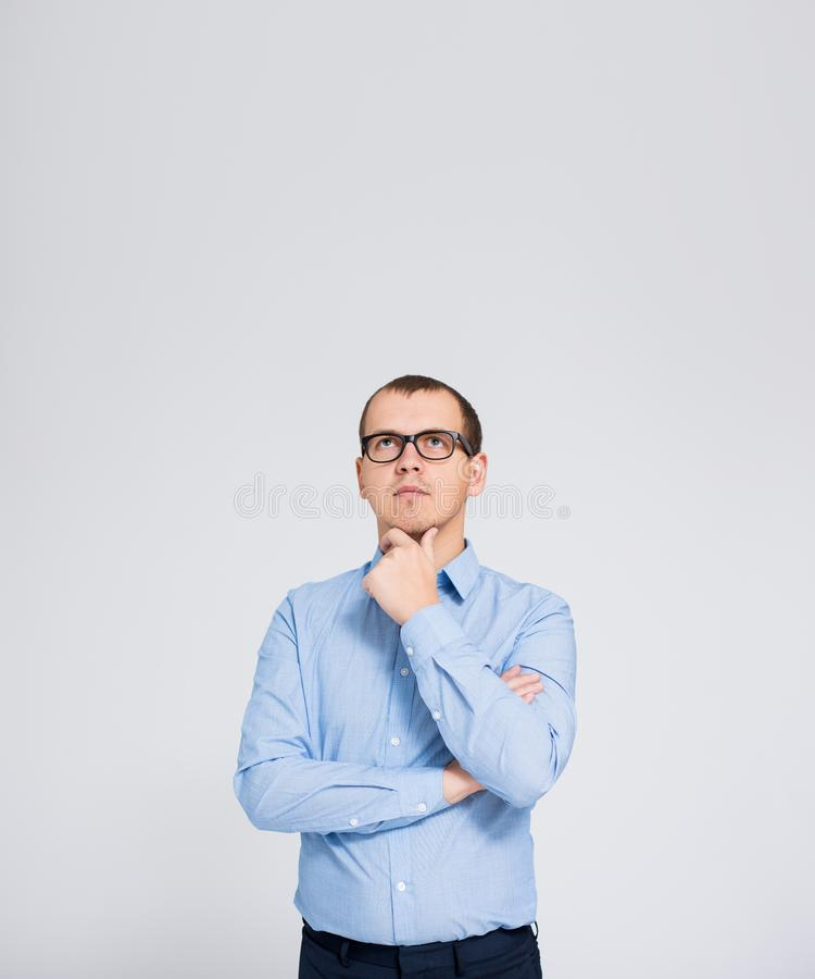 Idea concept - portrait of young thinking businessman and copy space over gray background stock image
