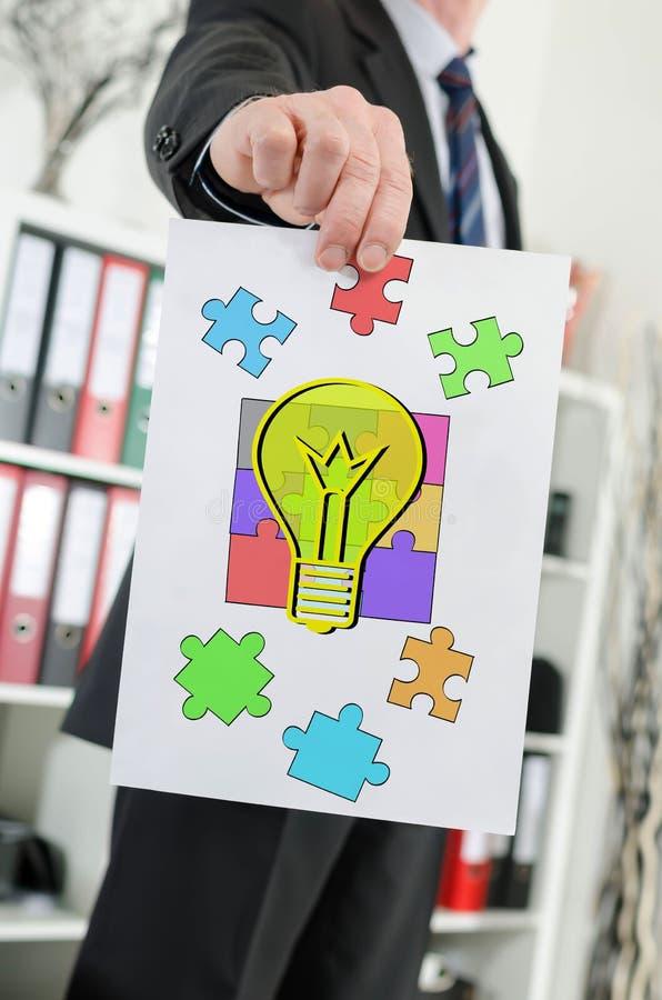 Idea concept shown by a businessman. Paper showing idea concept held by a businessman stock image
