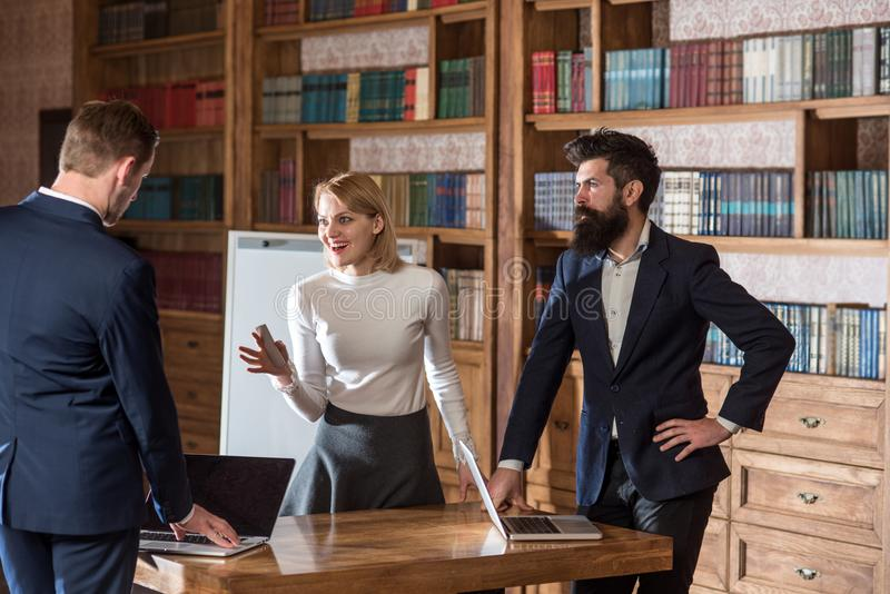 Idea concept. University students discuss new ideas in library. Businessmen and woman exchange business ideas. Focus on stock photo