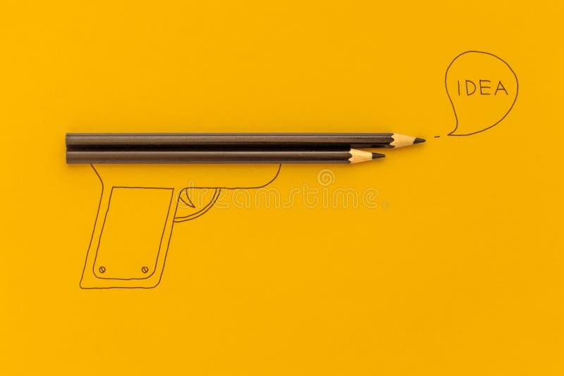Idea creative concept. Pencil gun on yellow background stock photography