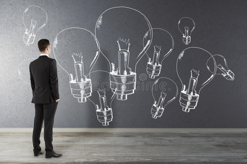 Idea and creativity concept. Back view of thoughtful young businessman in interior looking at concrete wall with drawn lamps.. Idea and creativity concept royalty free stock image
