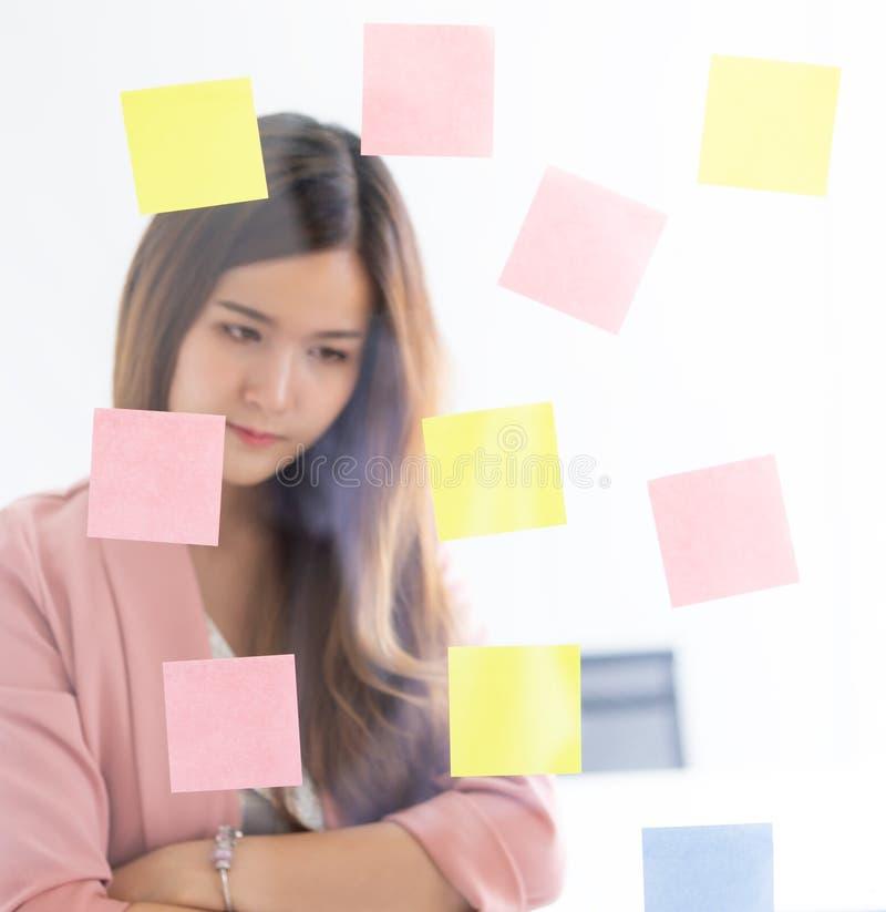 Idea de la escritura de la mujer de negocios encendido a las ventanas del post-it para el plan foto de archivo libre de regalías