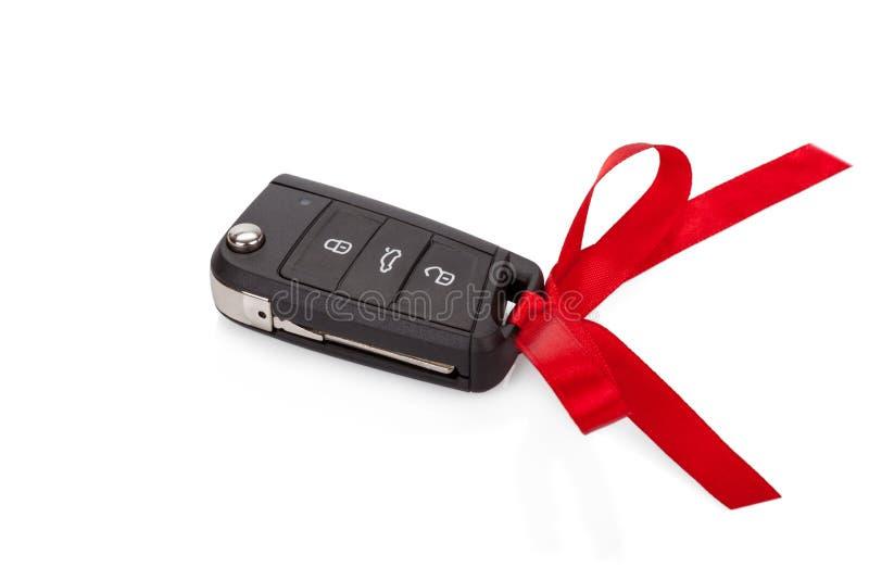 Idea del regalo: llaves del coche con la cinta roja aislada fotos de archivo libres de regalías