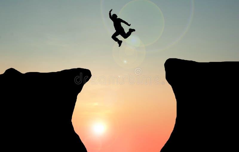 Idea di concetto della siluetta l'uomo che salta sopra la scogliera fotografia stock libera da diritti