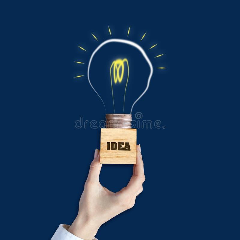 Idea di concetto La mano femminile tiene un blocco di legno con l'iscrizione, idea Lampadina su un fondo blu Il concetto di lumin royalty illustrazione gratis