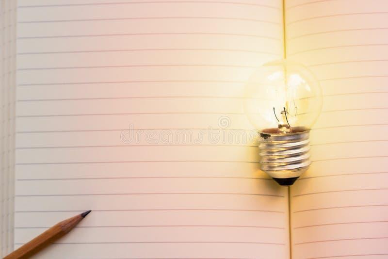 Idea di concetto Lampadina crescente sul libro d'annata con la matita Co fotografia stock