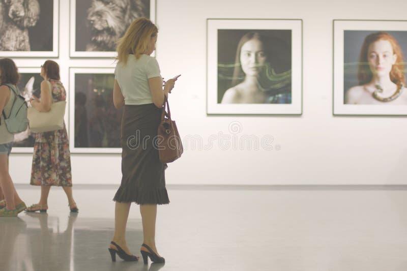 Idea di dipendenza del telefono cellulare La donna in galleria di foto non ascolta ma per mezzo del suo smartphone fotografie stock