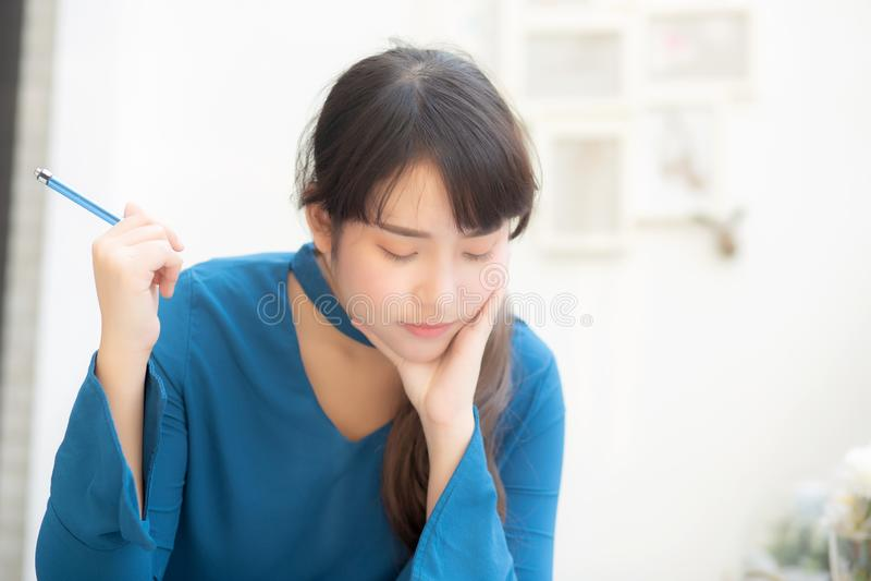 Idea di pensiero sorridente del bello del ritratto giovane scrittore asiatico della donna e scrivere sul taccuino o sul diario co immagine stock