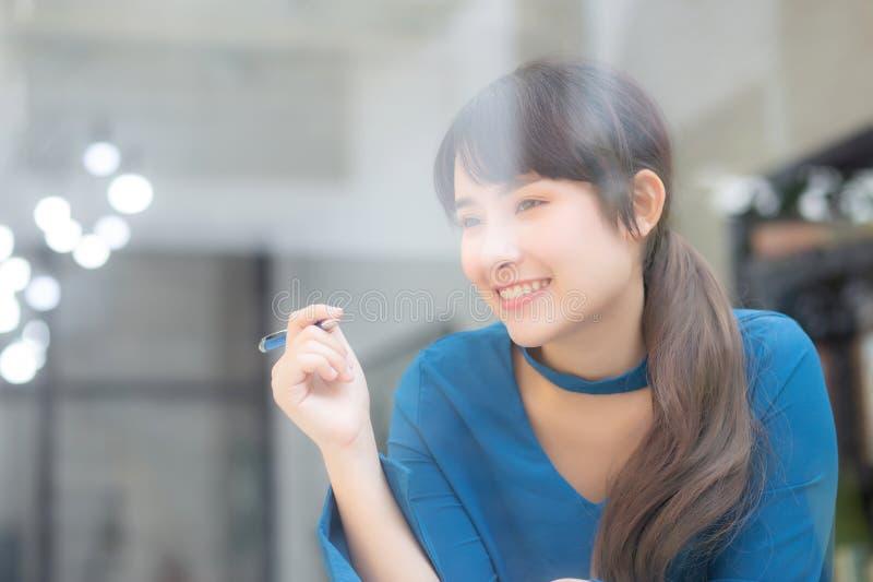 Idea di pensiero sorridente del bello del ritratto giovane scrittore asiatico della donna e scrivere sul taccuino o sul diario co fotografia stock libera da diritti