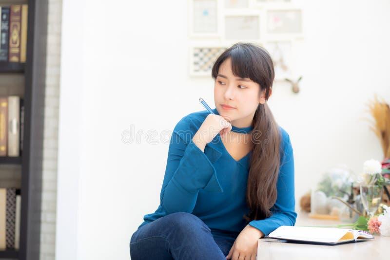 Idea di pensiero sorridente del bello del ritratto giovane scrittore asiatico della donna e scrivere sul taccuino o sul diario co fotografia stock