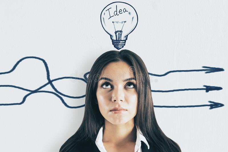 Idea and different direction concept. Portrait of attractive young european businesswoman with arrows and lamp sketch on white background. Idea and different royalty free stock photos