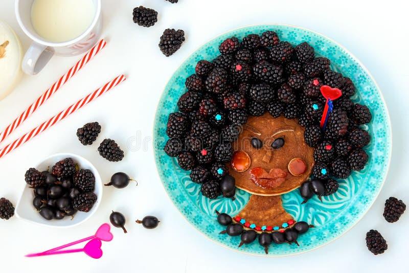 Idea divertente dell'alimento per la ragazza commestibile del negro dei bambini, il fronte dal pancake, l'uva spina e la mora, ar immagine stock libera da diritti