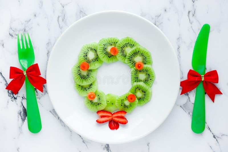 Idea divertida para los niños - guirnalda comestible de la comida de Navidad de la Navidad de la fresa del kiwi fotografía de archivo