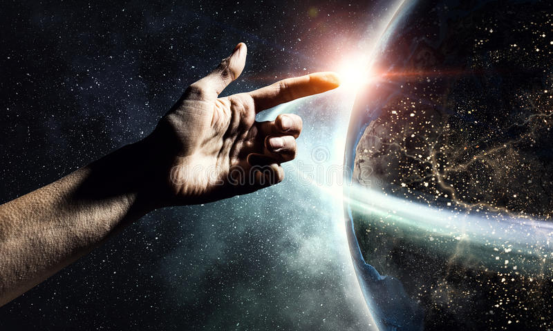Idea of Earth creation . Mixed media. Close of human hand touching with finger Earth planet. Elements of this image are furnshed by NASA royalty free stock image